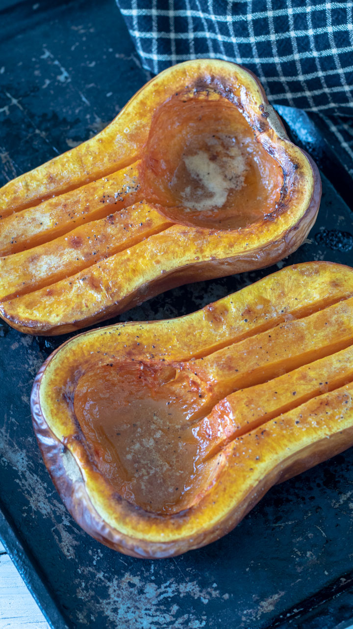 Butternut squash halves on metal baking sheet.