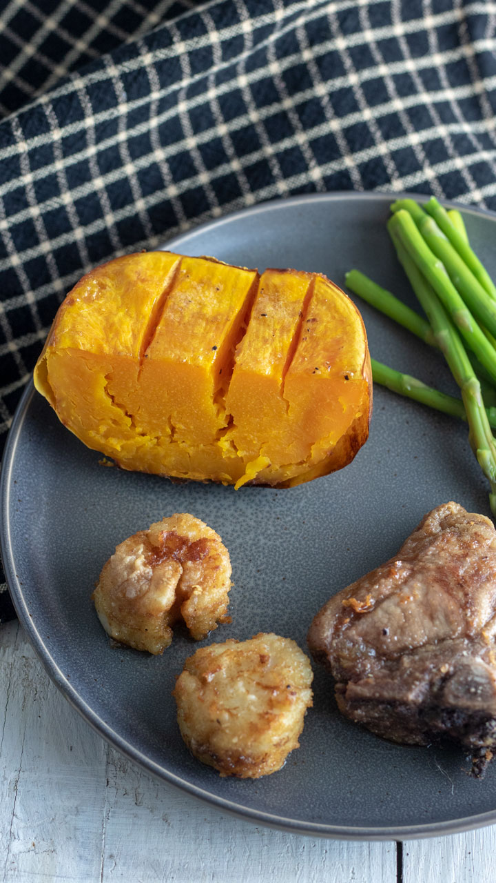 Slice of butternut on dinner plate with lamb chop.