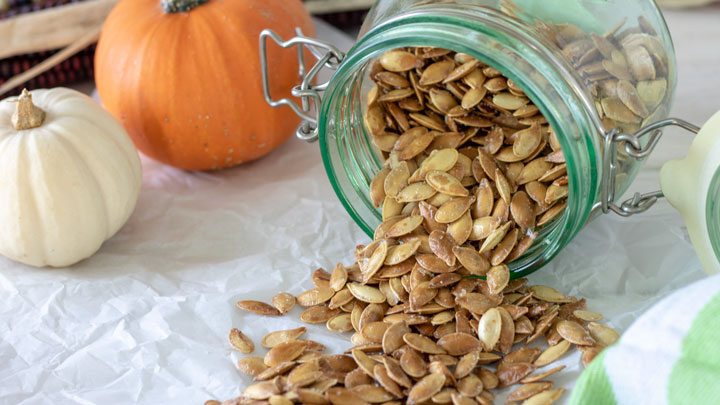 Roasted pumpkin seeds with small pumpkins.
