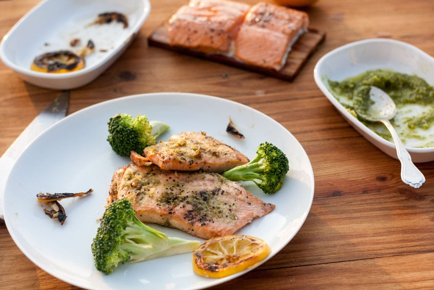 salmon with pesto on white plate with broccoli on wooden board