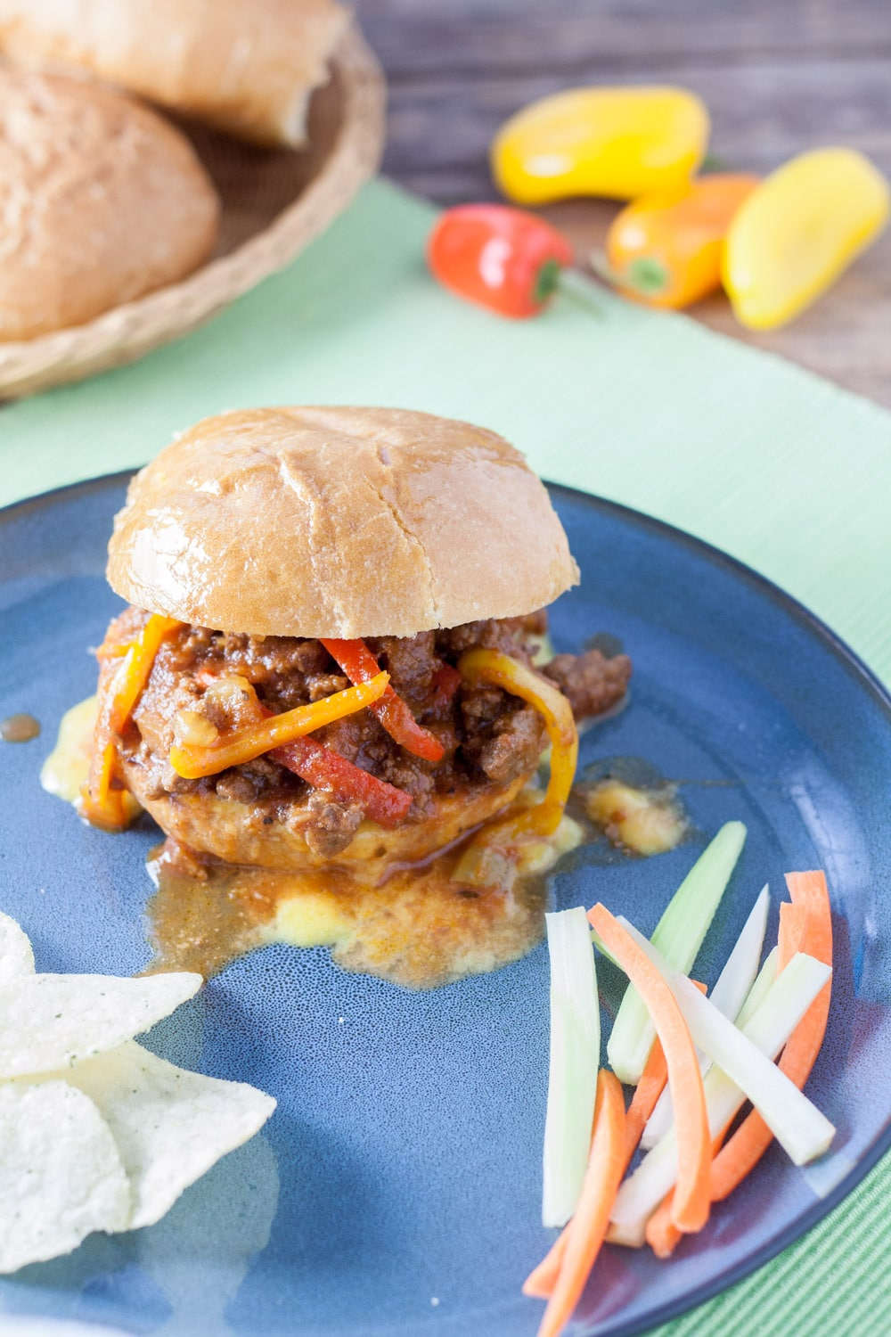 sloppy joes sandwich on blue plate with carrots, celery and chips