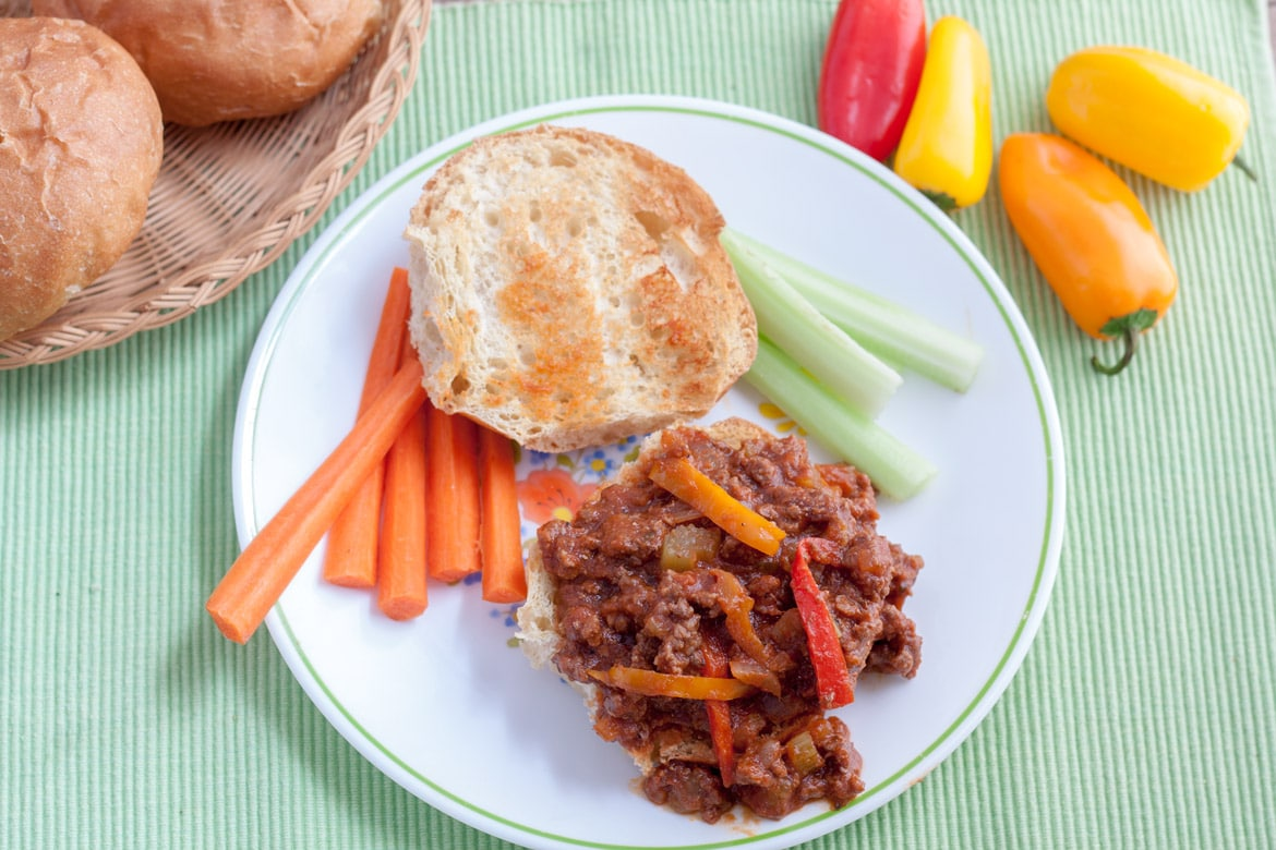 sloppy joes on white plate with rim border and carrots and celery