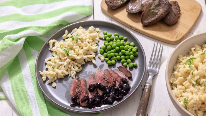 Spaetzle on grey plate served with duck breast.