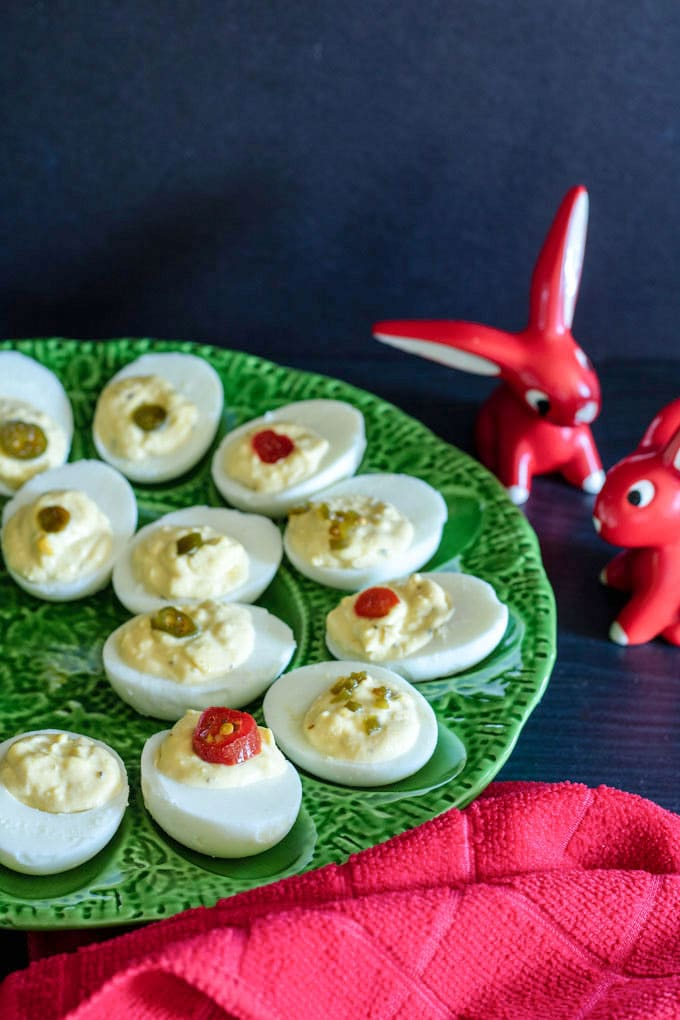 deviled eggs on green platter with red decorative rabbits