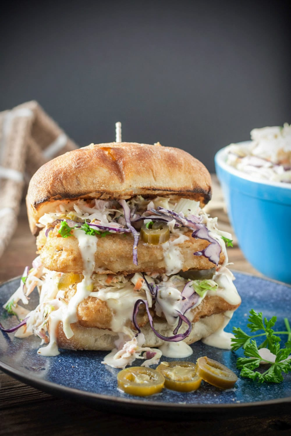 piled high fish sandwich with coleslaw and spicy aioli