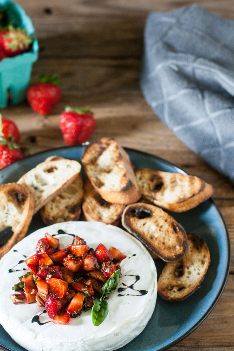grilled brie appetizer topped with strawberry and toasted crostini