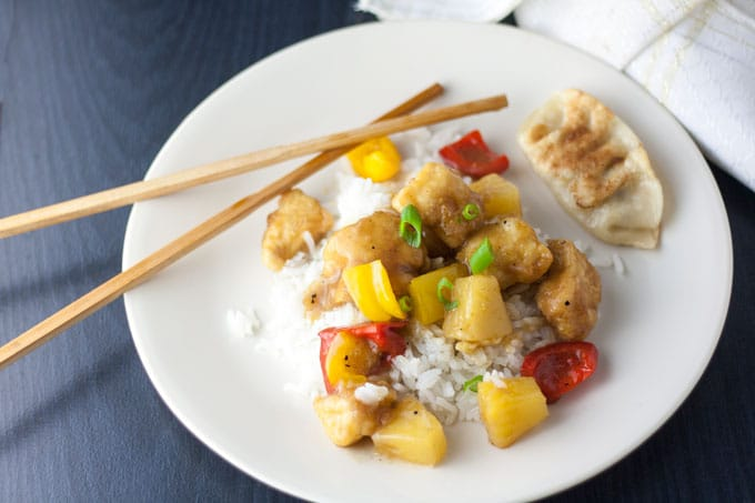 sweet and sour chicken with colorful peppers and pineapple chunks on white plate