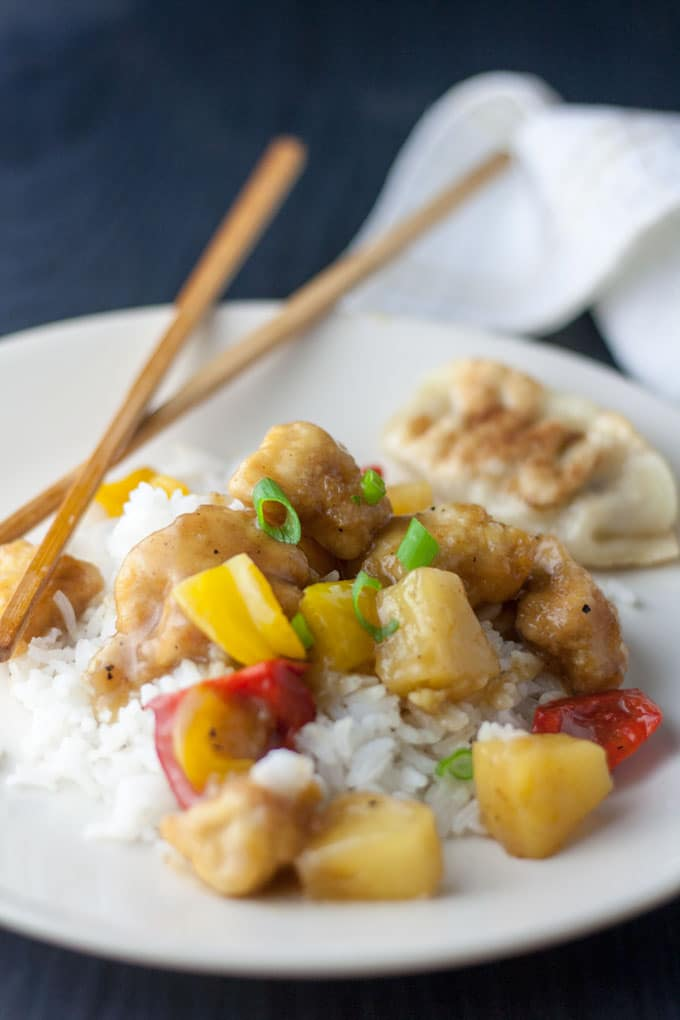 colorful sweet and sour chicken with rice and chopsticks