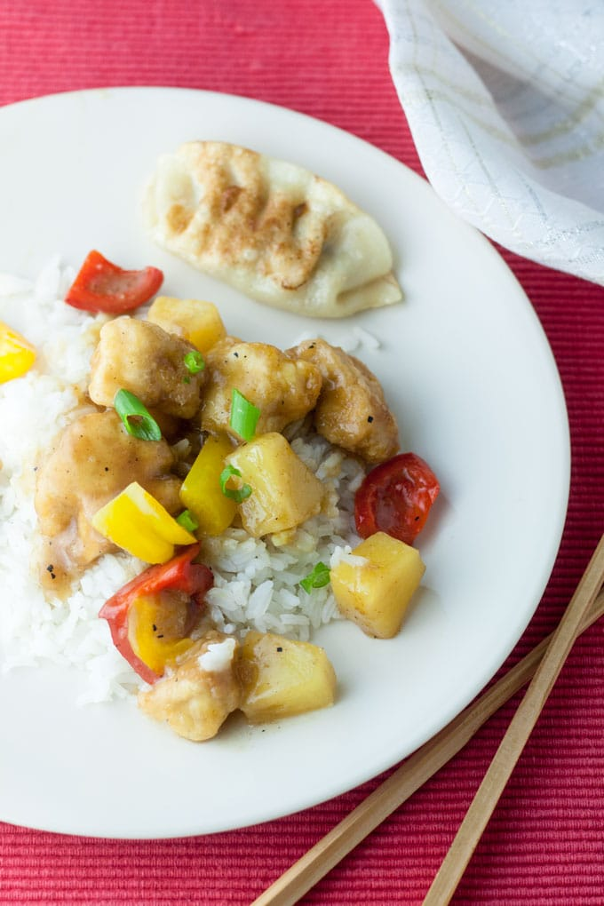 sweet and sour chicken with potsticker on red placemat