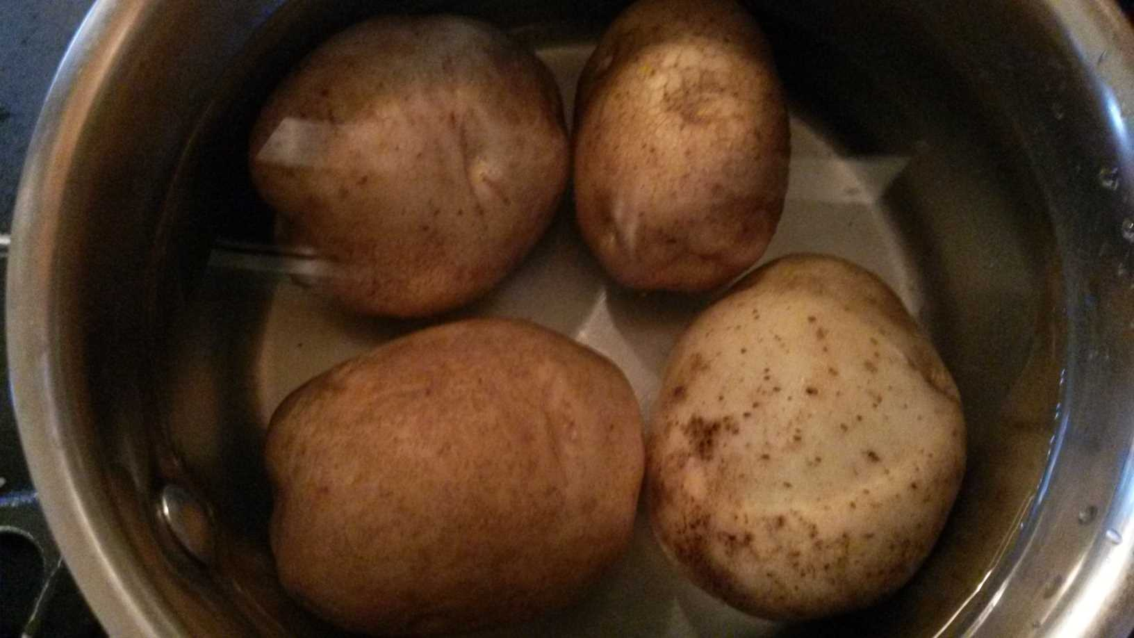 whole potatoes in pot, covered with water