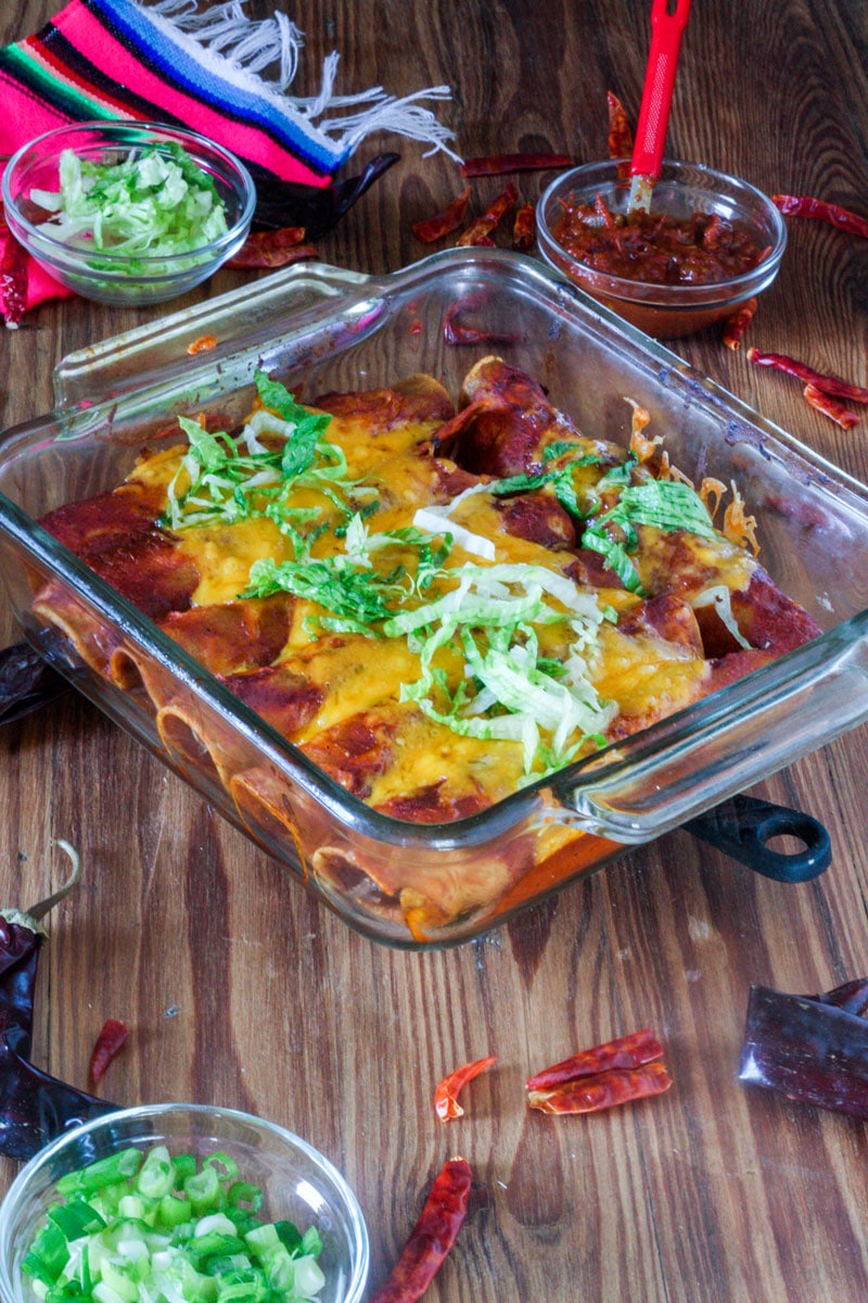 baking tray with cheese covered red enchiladas garnished with lettuce