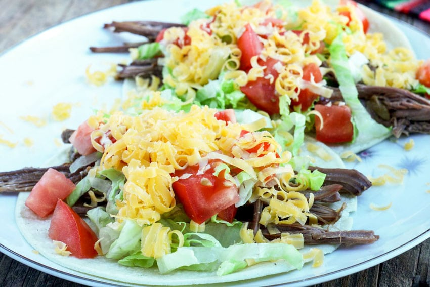 Close up of tostada with shredded venison, shredded lettuce, diced tomatoes and shredded cheese