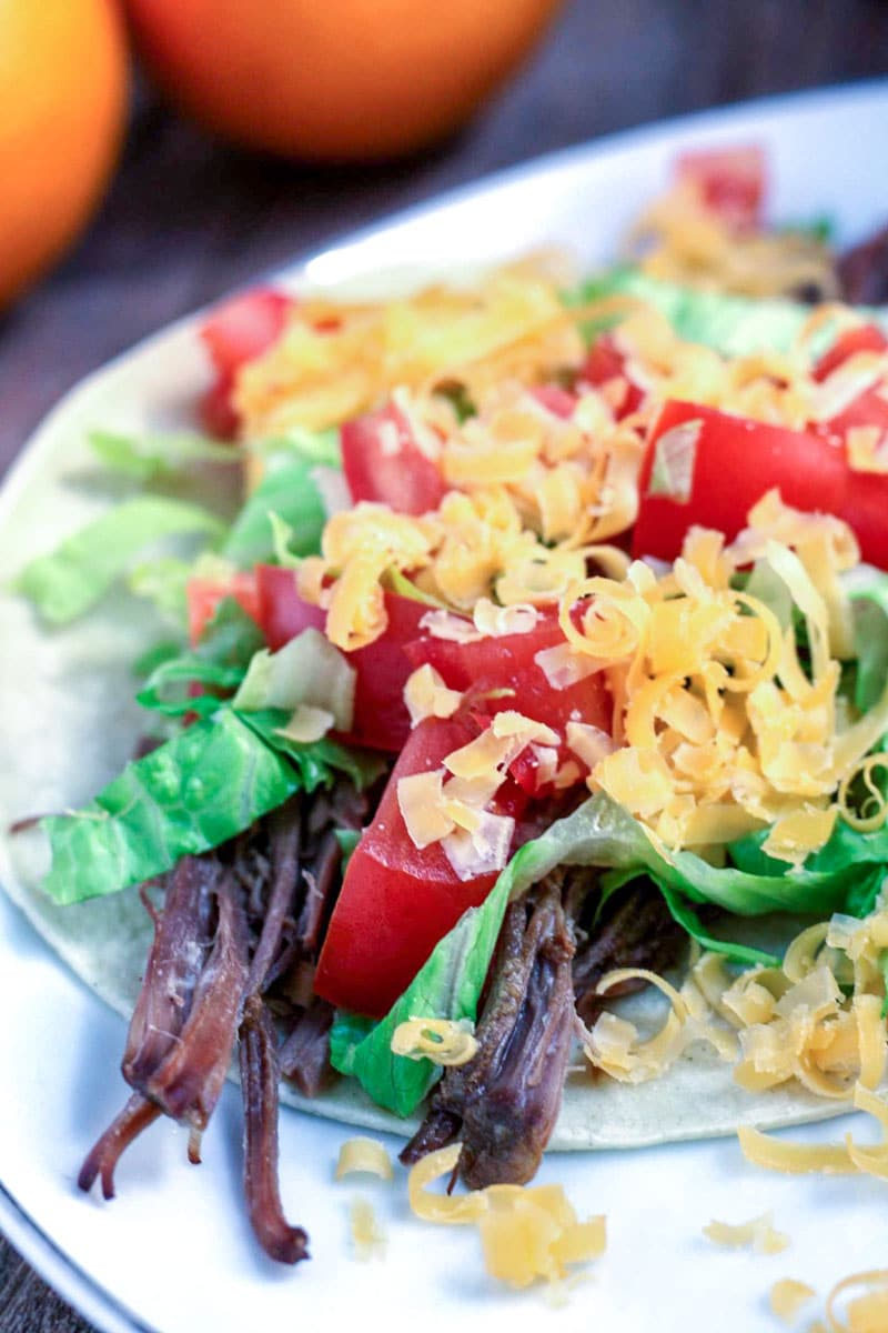 2 tostadas with shredde venison, shredded lettuce, diced tomatoes and shredded cheese