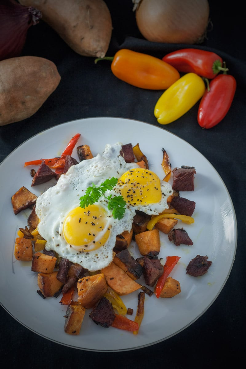 sweet potatoes, corned venison chunks with red yellow and orange peppers topped with 2 eggs