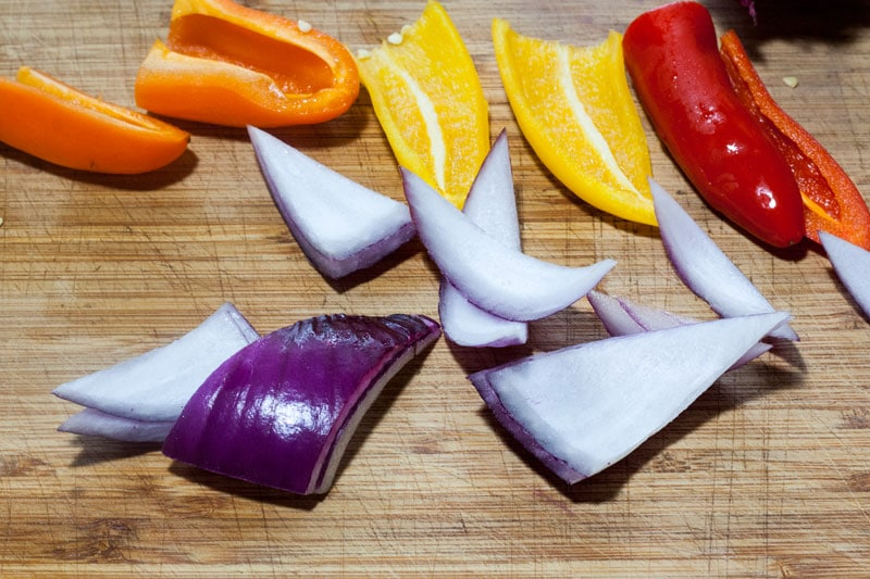 red onion and colored peppers on bamboo cutting board
