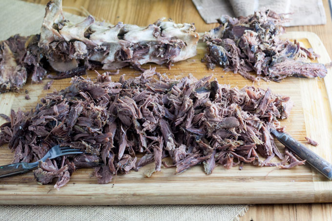 shredded meat on board with discarded bones