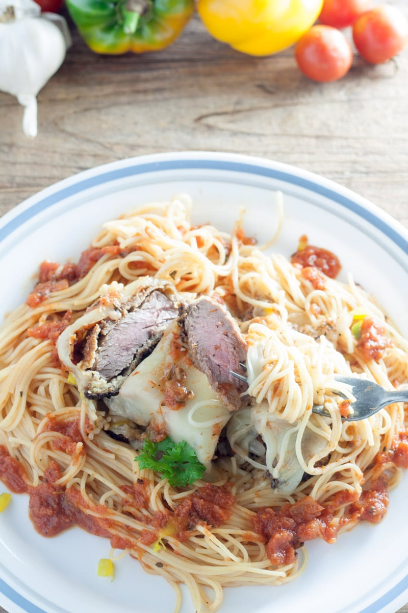 White plate with blue trim with pasta and red sauce with cut venison loin on a fork and topped with mozzerella