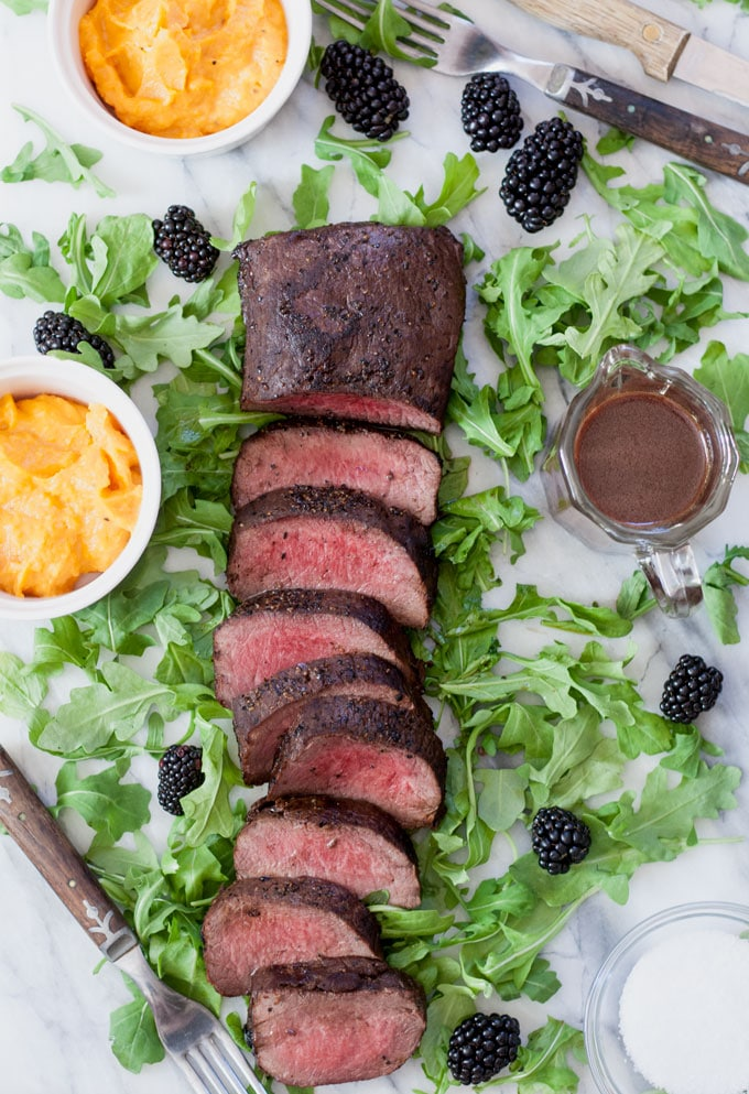 sliced venison loin with blackberry sauce on a bed of arugula