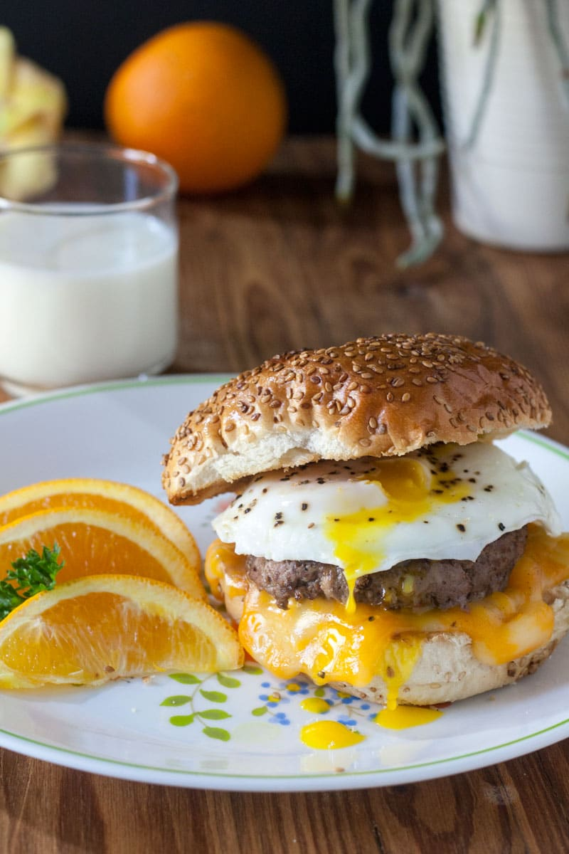 Close up of venison breakfast sausage sandwich on a toasted hard roll with melted cheese and egg yolk drips on side of sandwich