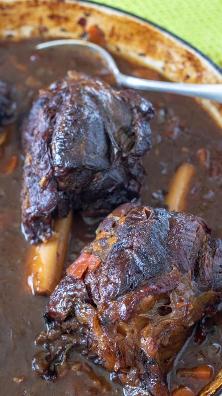 Close up of venison shanks in red wine sauce in Dutch oven.