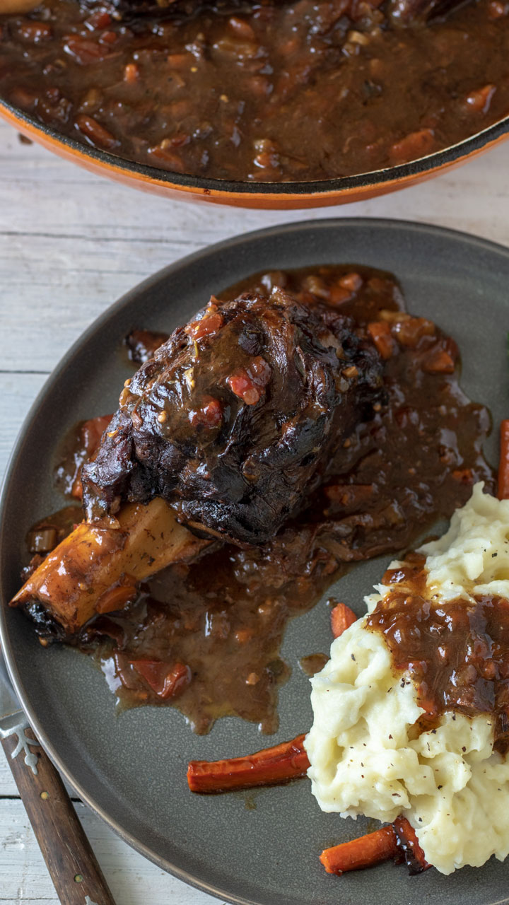 Venison shank of gray plate with carrots and mashed potatoes.