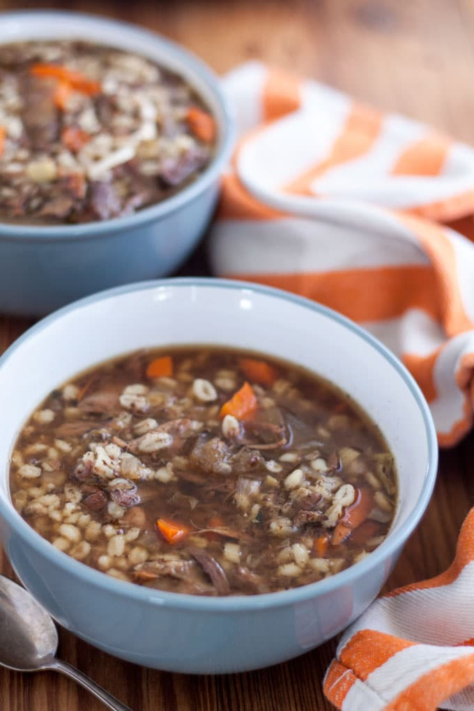 venison soup in grey bowl with orange and white towel background