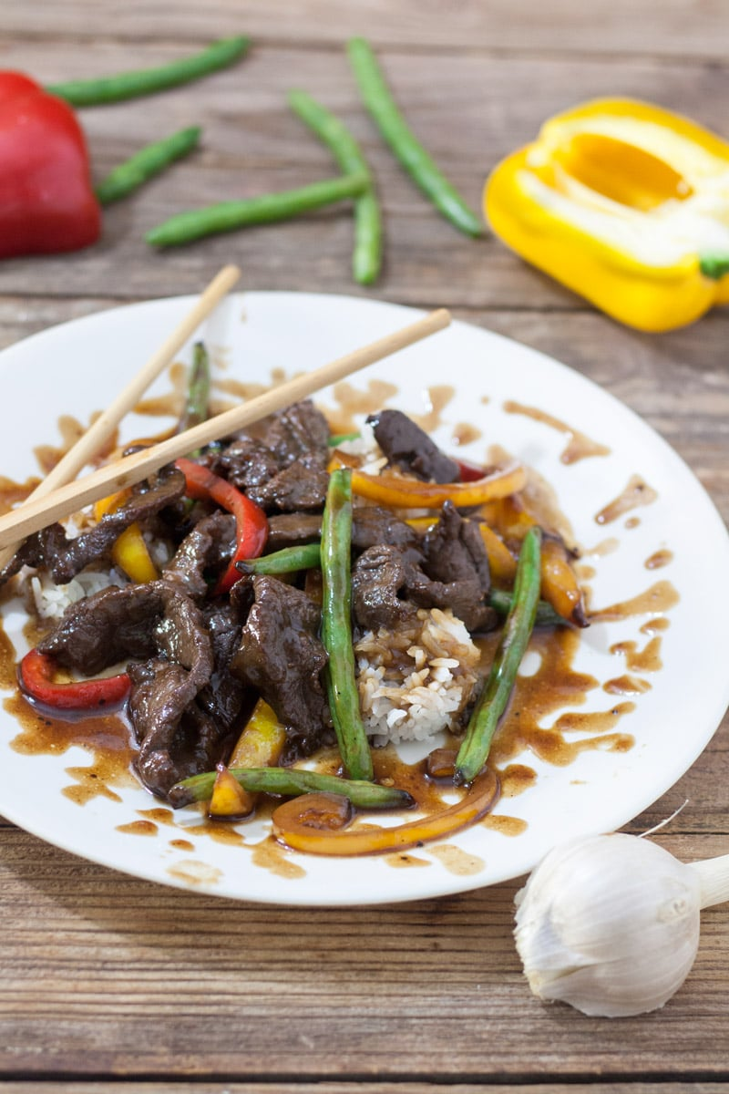 Venison teriyaki on white plate with red and yellow peppers and green beans