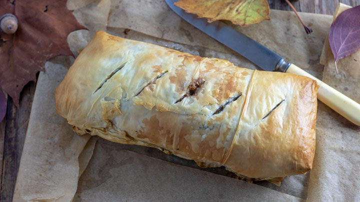 Whole venison wellington on paper with fall themed props.