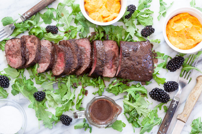 Sliced venison loin with blackberry sauce poured on top