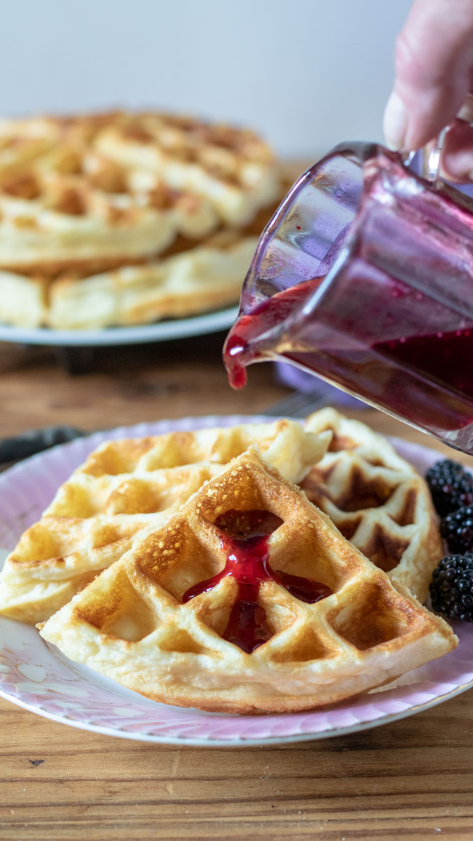 pink antique plate with waffles, hand pouring syrup