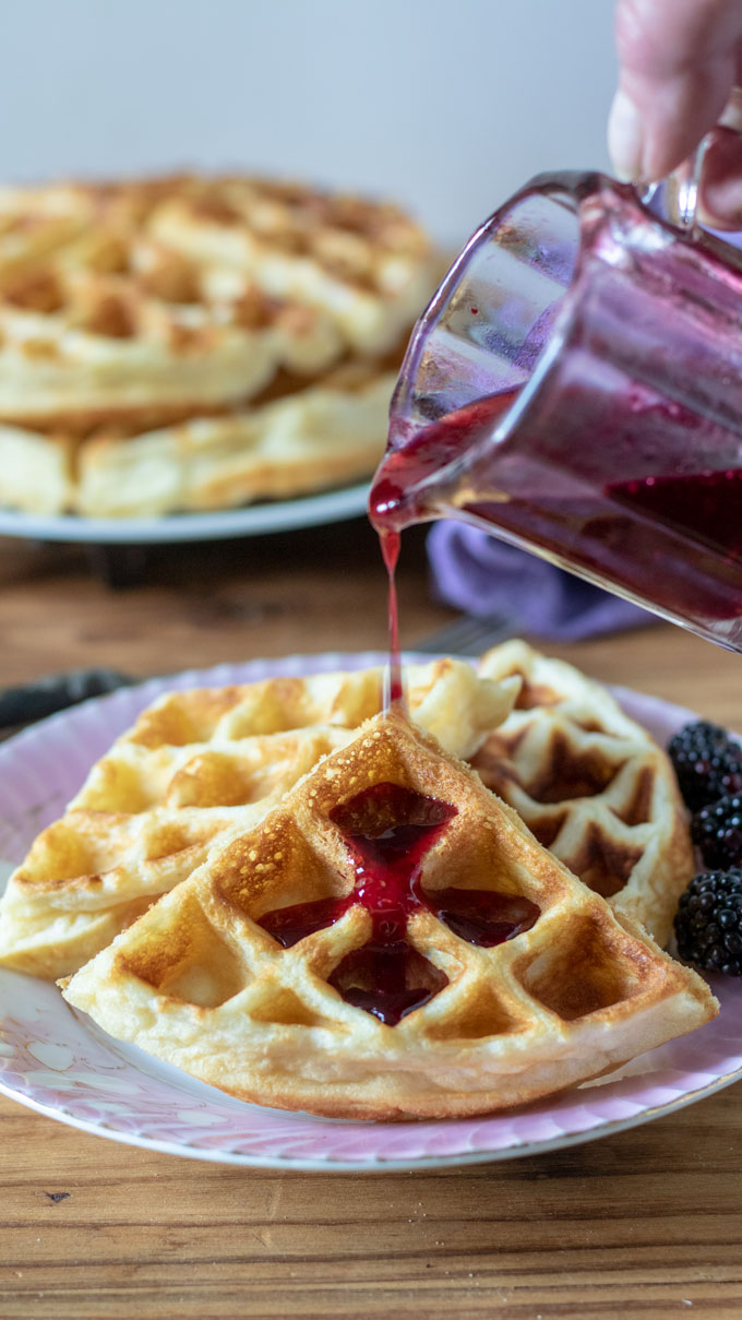 Blackberry syrup pouring on to waffles