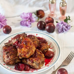 chicken with plum sauce and grilled plumes on white plate.