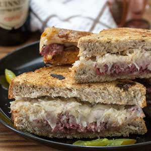 corned venison reuben sandwich recipe close up on black plate with pickles