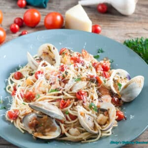 clams, shrimp, scallops in a fresh cherry tomato sauce on blue plate