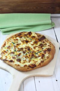 Tuna Florentine Pizza with Lemon, dill aioli on a wooden pizza peel near a light green tea towel