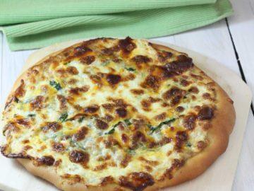 Tuna Florentine Pizza with Lemon, dill aioli on a wooden pizza peel near a light green tea towel