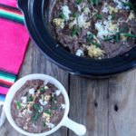 Slow Cooker Frijoles (Refried Beans ) Black bean refried beans in slow cooker topped with chopped chives and shredded cheeses