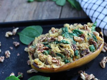 Spaghetti Squash, Parmesan, Bacon Boats on metal baking tray with spinach and walnuts