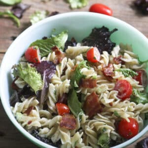 blt pasta salad in green bowl on wooden board