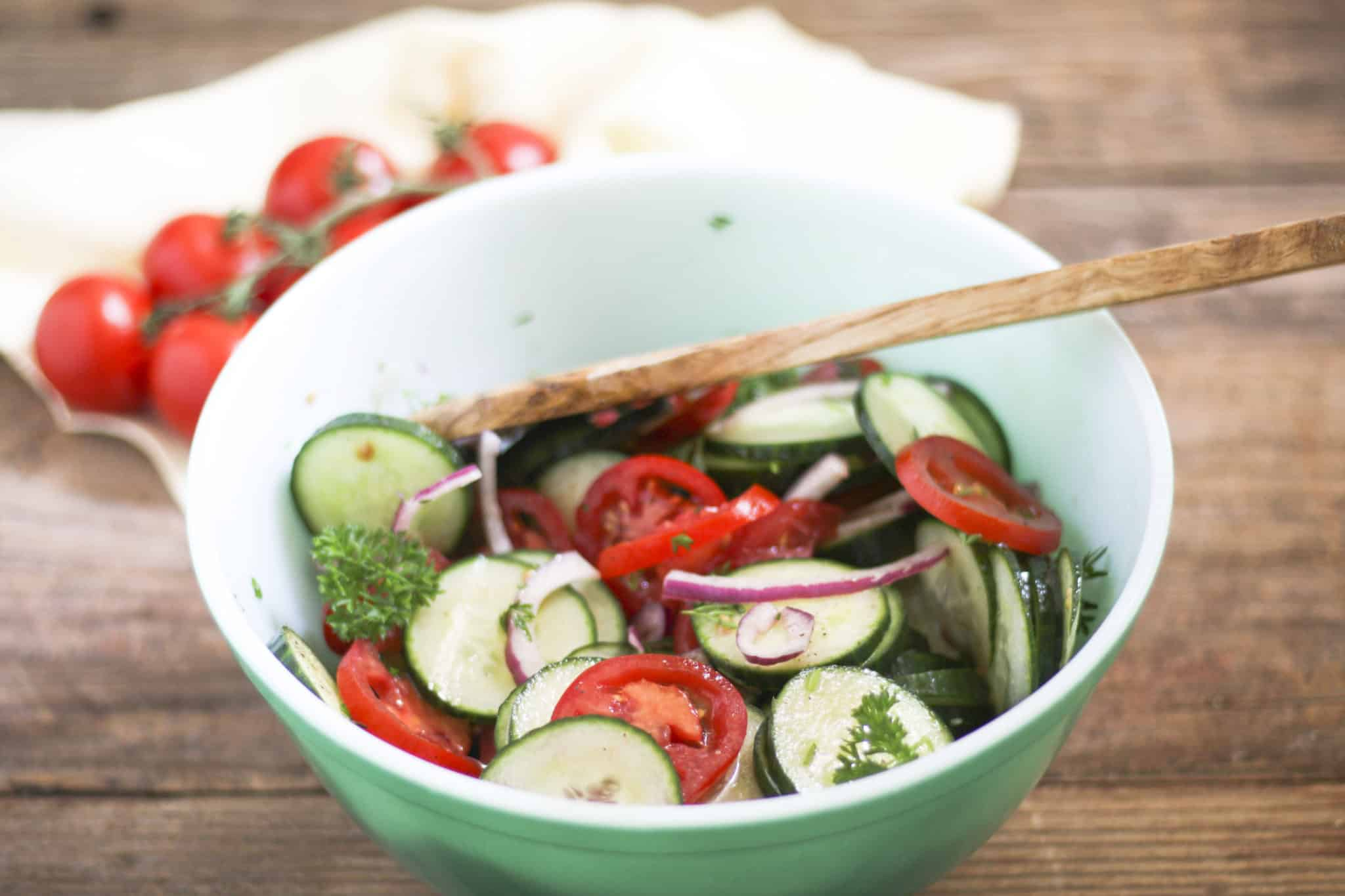 Sliced Cucumbers and Tomatoes in green bowl with red onion and a wood serving spoon
