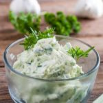 Butter in a small glass bowl with lots of green herbs running through it and parsley garnish