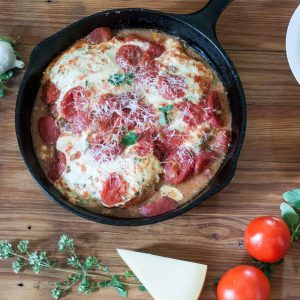 Cast iron pan filled with Chicken Capri Parmigiana with lots of cheese and tomatoes