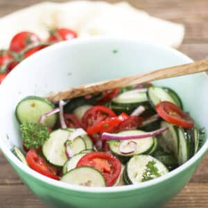 colorful cucumber and tomato salad in green bowl