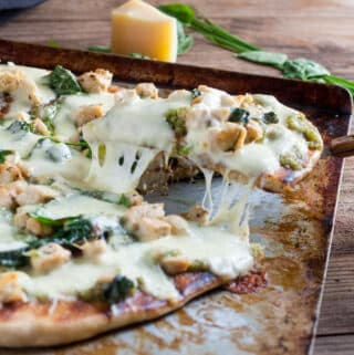 Thin crust Chicken Florentine Pizza with stringy cheese on a metal baking sheet