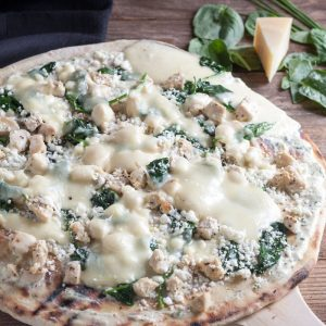 Thin Crust Chicken Pizza with Feta & Spinach on a wooden pizza peel