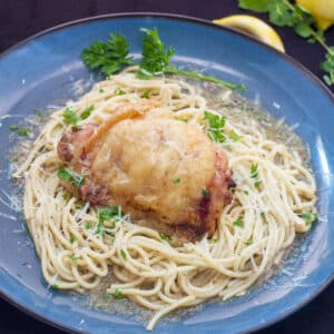 lemon chicken atop pasta on blue plate