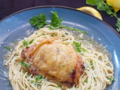 Eric's Lemon Chicken on a bed of spaghetti garnished with chives on a blue plate