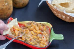 Canning Peach Salsa Red and green bowl shaped like pepper filled with colorful peach salad, with hand dipping chip into salsa