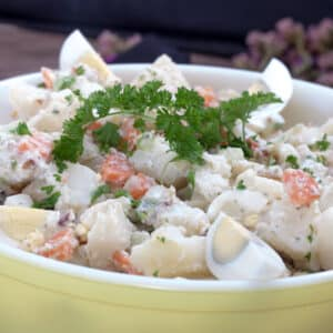 close up potato salad in yellow bowl