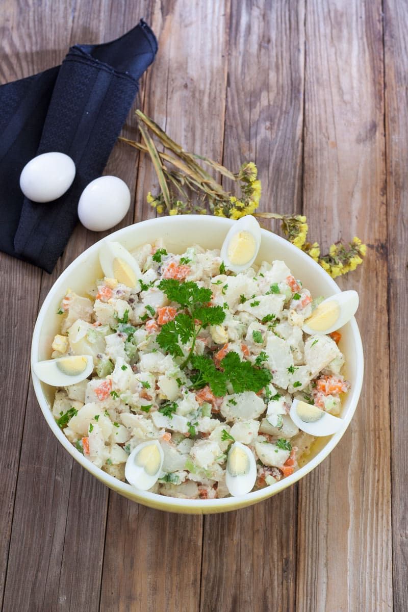 Mom's Bacon & Egg Potato Salad - Quarted hard boiled eggs rim a serving bowl with potato salad with carrots and celery and bacon bits garnished with chopped chives and parsley sprigs